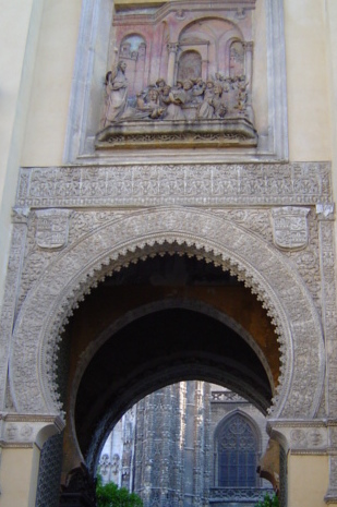 Christian relief above Moorish arch - the Puerta del Perdon, which leads of the Patio de Naranjos of the former mosque.