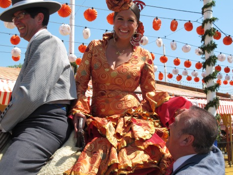I love this woman's bright orange dress, with the farolillos (paper lanters) behind.