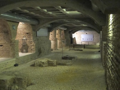 The crypt with its arched alcoves, or chapels, and remains of 13th-century church's floor.