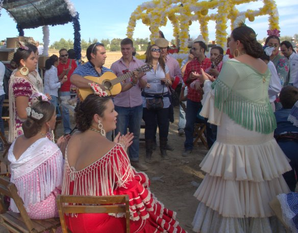 Clapping hands in time to the song, as men play the guitar. Romerias are about friendship, feasting and flamenca.