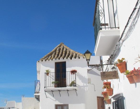 A typical street in Vejer, with its white walls, tield rooves, balconies and potted flowers.