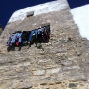 Washing hangs on the ancient walls of Vejer's fortress.